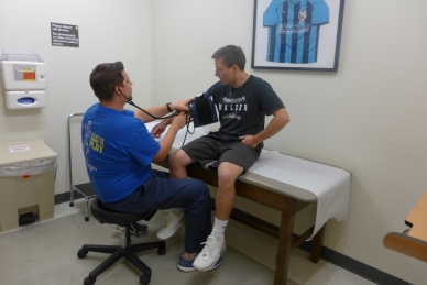 Nurse Practitioner Jacob Neal takes the blood pressure of Walker High School baseball player Camden Carver.